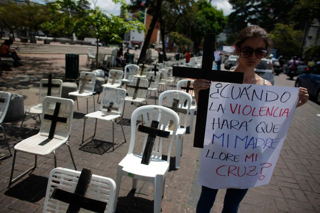 Anti-government protester holds a placard and a black cross, representing victims who died from violence, during a protest in Caracas