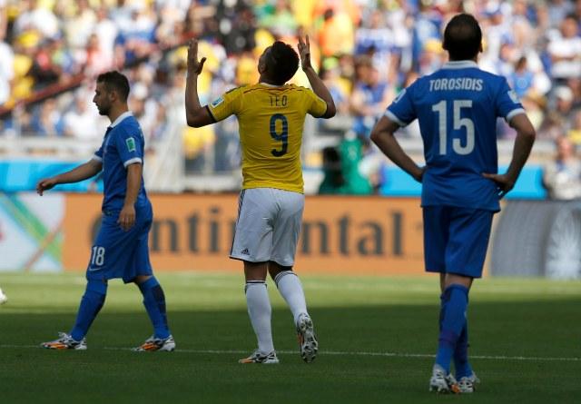 Greece's Fetfatzidis and Greece's Torosidis as Colombia's Gutierrez celebrates goal during 2014 World Cup soccer match in Belo Horizonte
