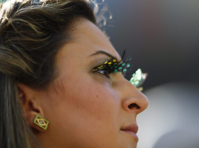 A Brazilian fan waits for the start of the opening ceremony of the 2014 World Cup at the Corinthians arena in Sao Paulo