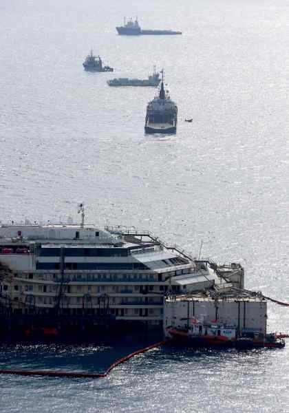 Cruise liner Costa Concordia is seen surrounded by tugboats during a refloat operation at Giglio harbour at Giglio Island