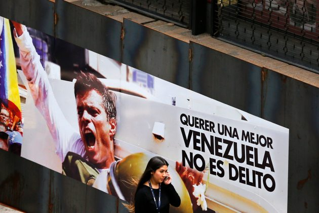 A woman walks past a banner with a picture of jailed opposition leader Leopoldo Lopez in Caracas