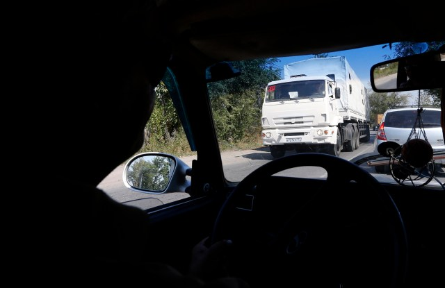 A truck of a Russian convoy carrying humanitarian aid for Ukraine is seen through a car window, as it drives in the direction of the Ukrainian border near the town of Donetsk, in Russia's Rostov Region
