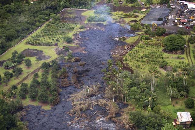 """Fotografía facilitada hoy, jueves 30 de octubre de 2014, que muestra la lava del volcán Kilauea, situado en la """"Isla Grande"""" del estado de Hawai (Estados Unidos), el 29 de octubre de 2014. La lava, que permanece a unas 100 yardas de la primera línea de casas, amenaza con arrasar la villa rural de Pahoa los próximos días aunque todavía no se ha dado la orden de evacuación. EFE/BRUCE OMORI/PARADISE HELICOPTERS"""