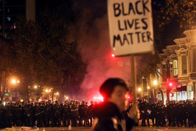 A line of police officers prepares to advance on protestors during a demonstration in Oakland, California