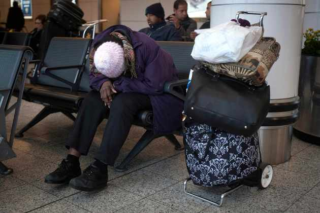 A woman sleeps at LaGuardia airport on the day before Thanksgiving in New York