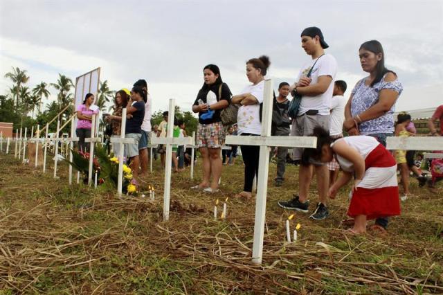 Un año después del tifón Haiyan, los filipinos que fueron víctimas de una de las peores tormentas de la historia intentan volver a la normalidad, pero muchos aún arrastran un trauma psicológico del que se niegan a hablar. En la imagen, familiares de las víctimas ante algunas de las miles de cruces blancas colocadas sobre la fosa común del Cementerio de la Sagrada Cruz, a las afueras de Tacloban, en memoria de unas 2.700 víctimas del tifón. Entre las endebles cruces de madera, donde los familiares de las víctimas escriben el nombre de los fallecidos con un simple rotulador, decenas de filipinos encienden velas y rezan por sus seres queridos con gesto afligido, pero muy pocos admiten estar pasando por un mal momento. EFE/Helen Cook
