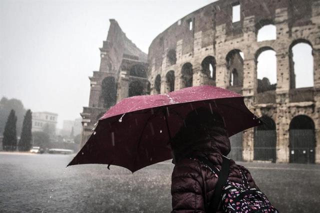 Una joven camina bajo la lluvia junto al Coliseo en Roma (Italia) hoy, jueves 6 de nviembre de 2014. Ayer se anunció el cierre de las escuelas de Roma y su provincia con motivo del temporal que hoy azota la capital italiana. En Roma y en la región del Lazio, a la que pertenece, están en alerta unas 1.200 personas pertenecientes a varias organizaciones de voluntarios para intervenir si fuera necesario en las próximas horas. EFE/Angelo Carconi