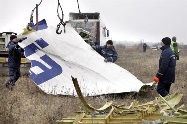 Trabajadores retiras un trozo del fuselaje del avión de pasajeros de Malaysia Airlines que fue presuntamente derribado por un misil en el este de ucrania, en Grabovo, a unos 70 km de Donetsk (Ucrania), hoy, martes 18 de noviembre de 2014. Expertos holandeses y funcionarios de los servicios de emergencia de la autoproclamada república popular de Donetsk (RPD) reanudaron ayer la recogida de restos del avión malasio en el que murieron las 298 personas que iban a bordo. EFE/Alexander Ermochenko
