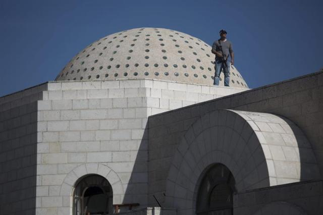 Un policía vigila en el tejado de la sinagoga tras el ataque contra una sinagoga en Jerusalén (Israel) hoy, martes 18 de noviembre de 2014. Al menos seis personas, entre ellas los dos presuntos atacantes, murieron hoy en un tiroteo en una sinagoga y yeshiva (seminario rabínico) del barrio ortodoxo de Har Nof, en Jerusalén Oeste, informó la Policía local. EFE/Abir Sultan