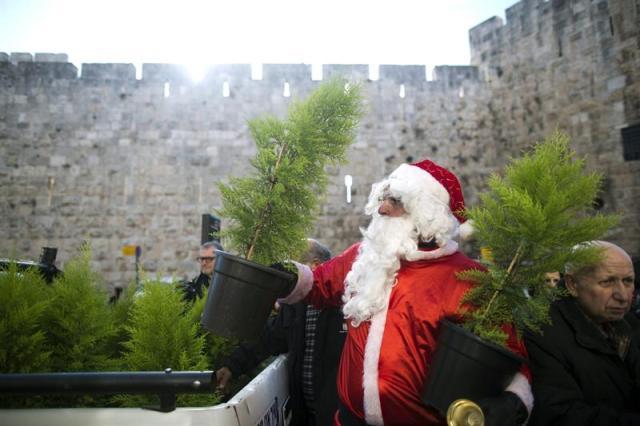 Un hombre vestido de Papá Noel vende árboles de Navidad en la puerta de Jaffa en la muralla de Jerusalén (Israel) hoy, lunes 22 de diciembre de 2014. EFE/Abir Sultan
