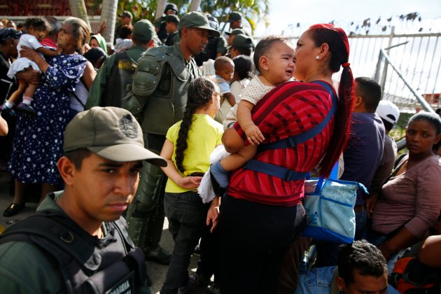 National Guards control access as people line up outside a state-run Bicentenario supermarket in Caracas