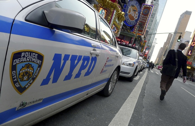 A pedestrian walks past a line of police cars parked at Times Square in New York
