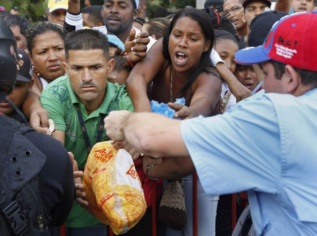 People crowd together in an attempt to buy chickens at a Mega-Mercal, a subsidized state-run street market, in Caracas