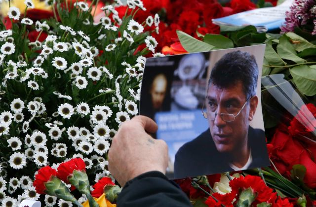 A visitor holds a photo at the site where Boris Nemtsov was recently murdered, in central Moscow