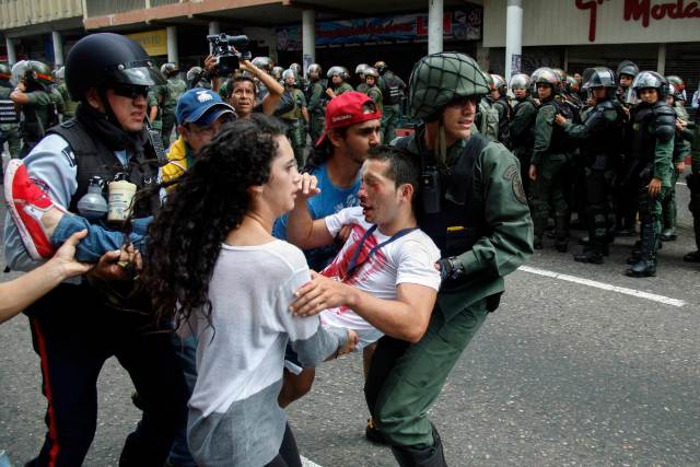 An opposition students is carry away after being injured during against President Nicolas Maduro's government in San Cristobal