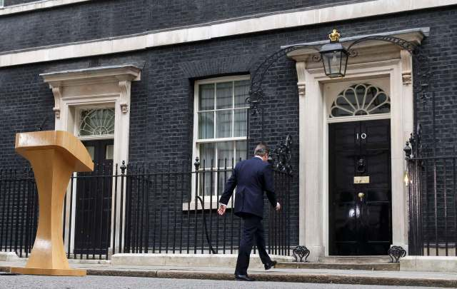 Britain's Prime Minister David Cameron walks back into 10 Downing Street after speaking upon his return after meeting with Queen Elizabeth at Buckingham Palace in central London