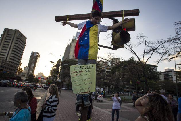 Un hombre se amarra simulando una crucifixión a modo de protesta contra el Gobierno venezolano, en el semáforo de una plaza hoy, miércoles 4 de marzo de 2015, en Caracas (Foto EFE)
