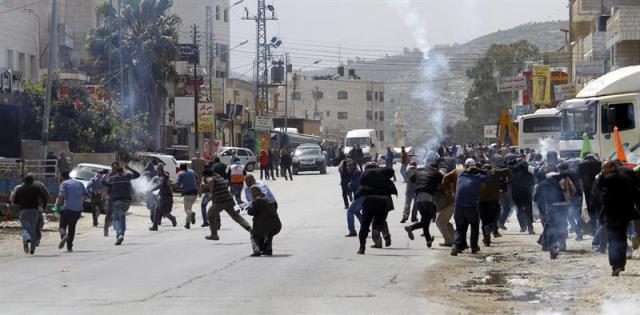 """Un grupo de manifestantes palestinos huye de los botes de gas lacrimógeno lanzados por la policía israelí durante una protesta que ha causado disturbios en el """"Día de la Tierra"""", jornada en la que los palestinos protestan por la expropiación de sus tierras, en Howara, cerca de la ciudad de Nablus (Cisjordania) hoy, lunes 30 de marzo de 2015. Distintas localidades árabes del norte y sur de Israel albergarán hoy actos y marchas destinadas a rememorar el 39 aniversario de la muerte en Galilea de seis palestinos con ciudadanía israelí que participaban en una protesta contra la confiscación de sus terrenos y la judaización de la región. EFE/Alaa Badarneh"""