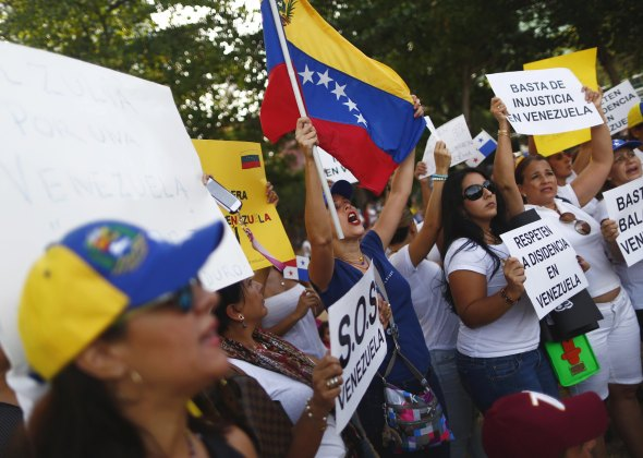 Venezuelan residents in Panama yell slogans and hold signs during a protest against Venezuela's President Nicolas Maduro ahead of his arrival for the Summit of the Americas, in Panama City