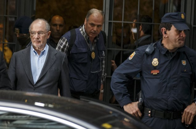 Rato, former People's Party minister and former managing director of the International Monetary Fund, is lead by police as they leave his residence after an inspection in Madrid