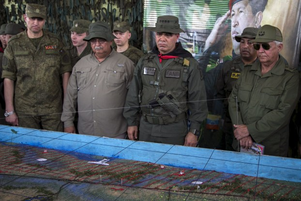 Russian Army general, Dragovaloskiy, Apure's governor, Carrizales, Venezuela's Defense Minister Padrino Lopez and Revolutionary Forces of Cuba General, Quintas, look at a model, during a military exercise in the state of Apure