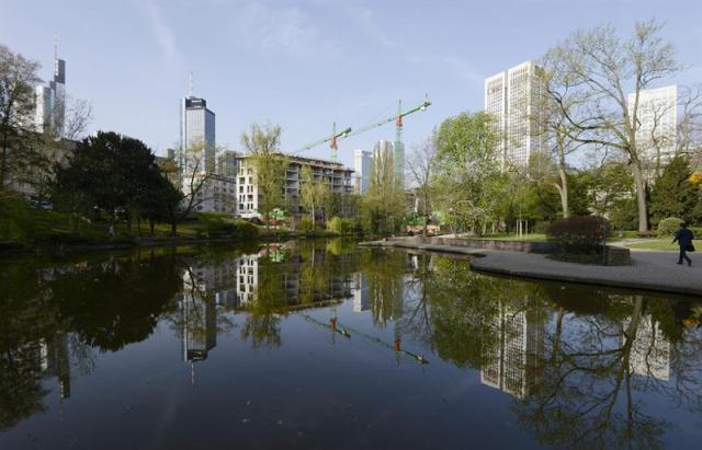 Un peatón (d) se dirige a su lugar de trabajo en Fráncfort (Alemania) hoy, jueves 16 de abril de 2015. Los principales institutos de estudios económicos alemanes han revisado al alza el pronóstico de crecimiento del PIB de Alemania para 2015 y creen que tendrá un fuerte repunte, impulsado ante todo por el consumo privado. Según el informe conjunto de los institutos DIW de Berlín, IFO de Múnich, IWH de Halle y RWI de Colonia, que se presenta hoy y ha sido adelantado por varios medios alemanes, el producto interior bruto (PIB) alemán crecerá este año un 2,1 % y en 2016 un 1,8 %. El pronóstico de crecimiento del informe otoñal para este año era del 1,2 %. Sin embargo, la eficiencia de la economía alemana se ve limitada en una comparación internacional por las excesivas cargas fiscales para los trabajadores. EFE/Mauritz Antin