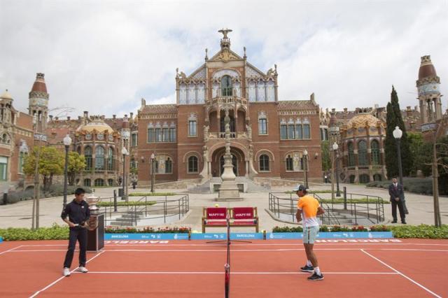 Los tenistas Rafa Nadal (d) y Key Nishikori (i) pelotean hoy en el recinto modernista del hospital de Sant Pau de Barcelona, durante la presentación del Barcelona Open Banc Sabadell, que este año celebra su edición 63. EFE/Alejandro García