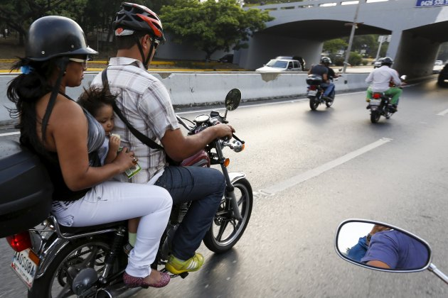 A girl drinks juice on a motorcycle while being driven on a highway in Caracas
