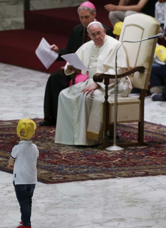 """A boy from the """"Fabbrica della Pace"""" group approaches Pope Francis as he holds an audience at the Vatican"""
