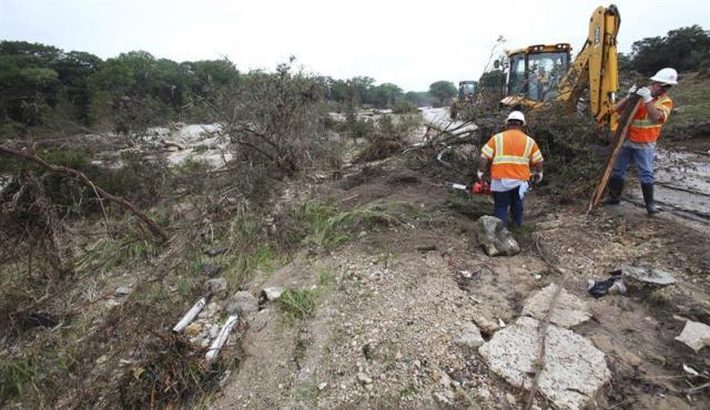 Dos trabajadores del condado de Hays limpian los escombros provocados por las fuertes lluvias e inundaciones que azotaron Wimberly, en Texas (Estados Unidos), hoy, 27 de mayo de 2015. El número de víctimas mortales por las fuertes tormentas y las inundaciones que azotaron a Texas y Oklahoma en los últimos tres días ascendió a 16, una cifra que las autoridades temen que aumente ya que hay una docena de desaparecidos. EFE/STEPHEN SPILLMAN
