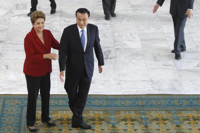 La presidenta brasileña, Dilma Rousseff (i), recibe al primer ministro de China, Li Keqiang (d), hoy, martes 19 de mayo de 2015, en el Palacio presidencial de Planalto en Brasilia (Brasil). Rousseff recibió con honores de Estado a Li Keqiang, quien inicia en Brasilia una gira que le llevará también a Colombia, Perú y Chile. Li llegó a Brasilia la noche de este lunes y hoy se dirigió al Palacio presidencial de Planalto, donde, tras pasar revista a tropas del Batallón de Dragones de la Independencia, fue recibido con un apretón de manos por la mandataria brasileña en lo alto de una rampa que conduce al primer piso de la sede del Gobierno. EFE/Fernando Bizerra Jr