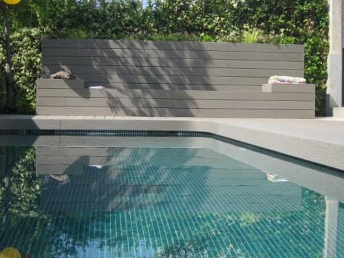 Tarima gris en piscina con banco