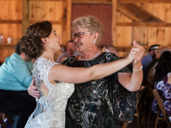 Bride and grandmother dance at barn wedding