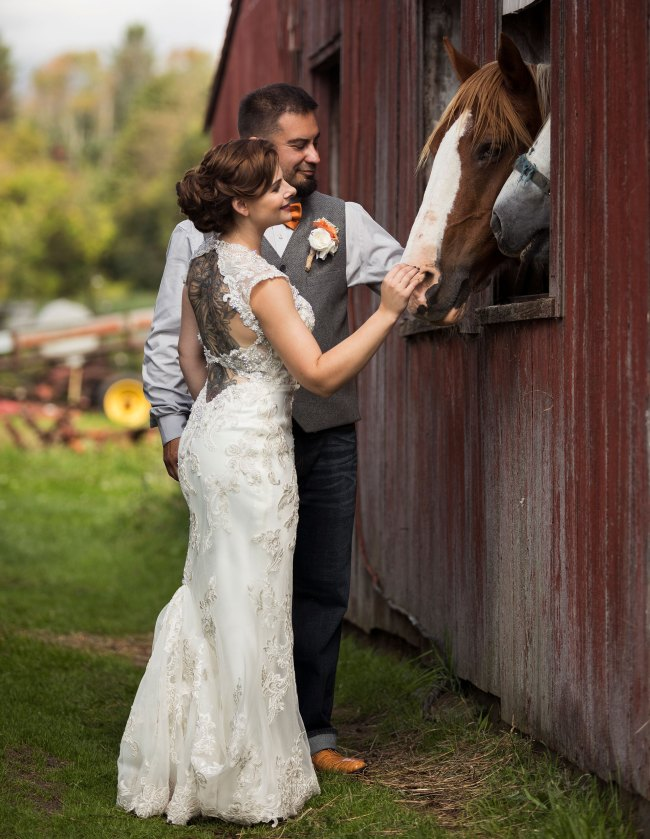 bride and groom greet horses on their wedding day