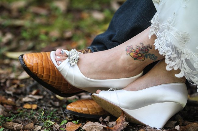 Bride and groom's shoes with ankle tattoo