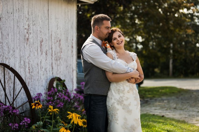 bride and groom in front of white barn