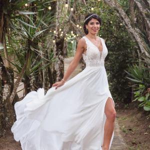 Chica caminando en vestido de novia mostrando la pierna y con escote profundo