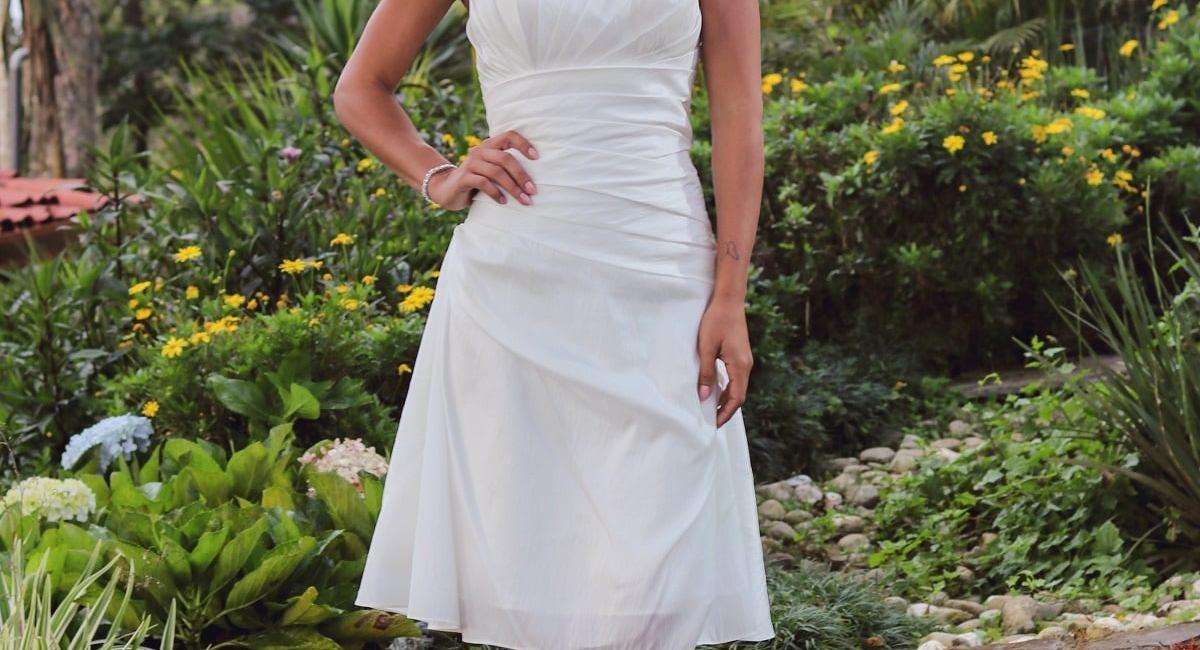 Chica posando con vestido blanco corto en naturaleza