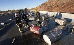 Bomberos de Murcia trabajando, en la tarde de ayer, en la retirada de los bidones que perdió el camión en el derrape.