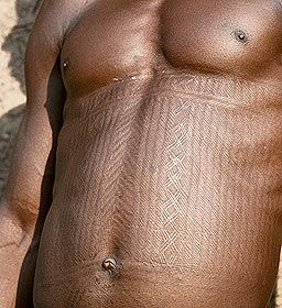 In Bétamarribé iconography, crisscross patterns (like the letter X) and ribbed designs that resemble the raised scar patterns seen on men's chests are symbols of Fayenfe, the god of war and death. This god serves as the patron deity for persons who have come in close or frequent contact with death – tomb diggers, warriors, and certain healers. Fayenfe is believed to ease the trauma of death for such persons and to protect them and the community from various dangers associated with the dead. I think that the ribbed and crisscross patterns carved into the chests of some Bétamarribé men seem to suggest the idea of a barrier, a protective bar or series of bars that perhaps prevented evil spirits (and death) from entering the human body. Similar signs are also carved into the plastered walls of Bétamarribé houses by men to identify that their patron deity is Fayenfe.