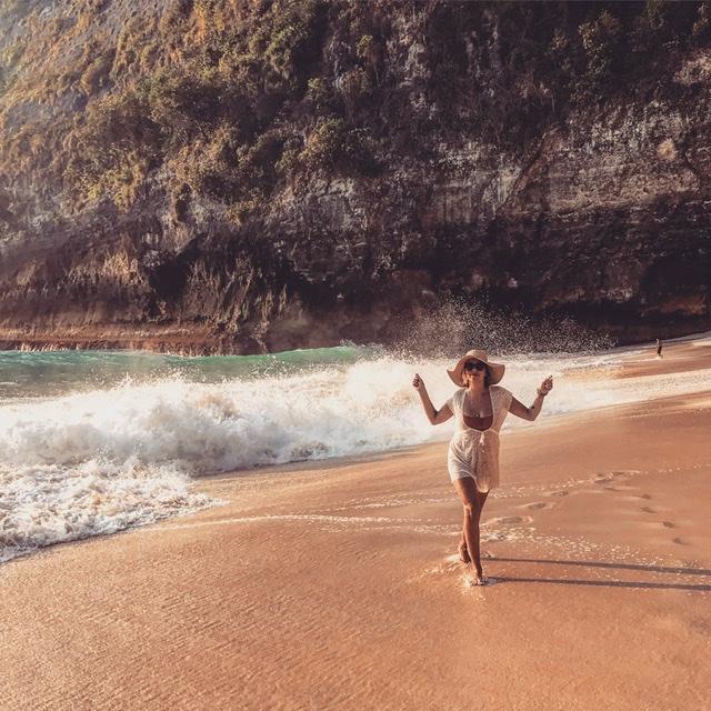 Sara Erb tanzt fröhlich am Kelingking Beach in Nusa Penida, während die hohen Wellen an die Küste peitschen.