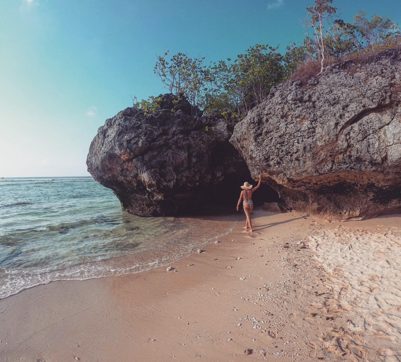 Zwischen den Felsen des Padang Padang Strandes auf Bali nahe Uluwatu mit Sonnenhut und Bikini.