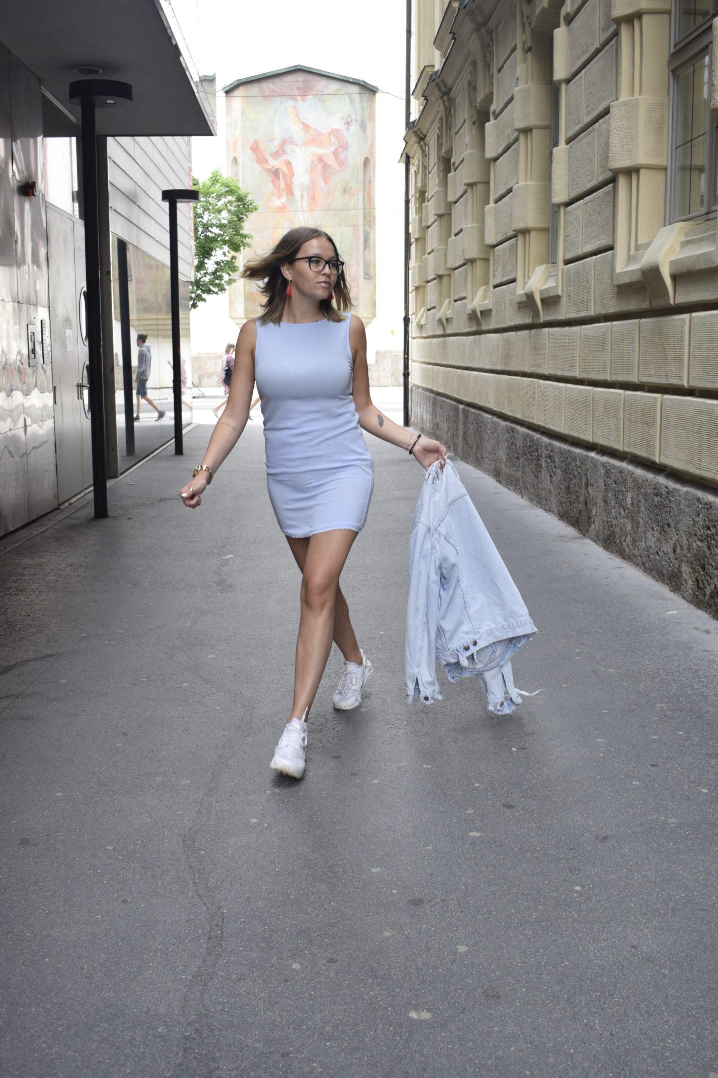 Sara Erb hüpft fröhlich in einem hellblauen Minikleid und mit Vintage Jeansjacke durch Innsbruck.