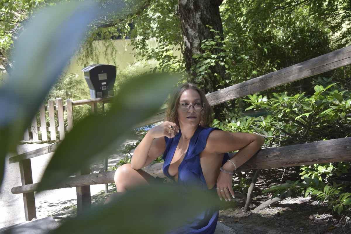 Keinen BH tragen: Wieso und was das Tragen eines BHs für gesundheitliche Risiken mit sich bringt, erklärt La Sara Leona aka Sara Erb aus Innsbruck in Tirol in diesem Beitrag. Sie trägt ein tief ausgeschnittenes dunkelblaues Rüschenkleid ohne BH, kombiniert mit einer Furla Mandarino Tasche.