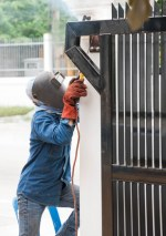 Contractor Supporting Services: sparking worker working on metal gate