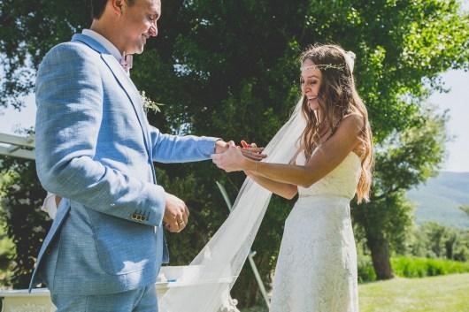 La mariée mets l'alliance au doigt de son mari