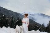 Mariée rousse à la montagne avec un chien blanc