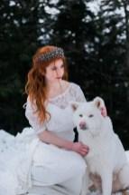 Mariée rousse dans la neige avec un chien blanc