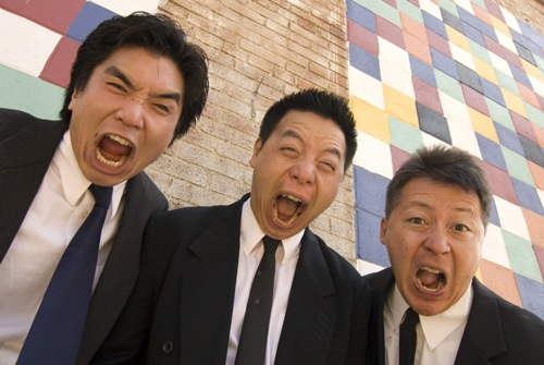 Three Asian American men wearing dark suits form a line looking down at the camera, mouths open as if in a yell or scream.