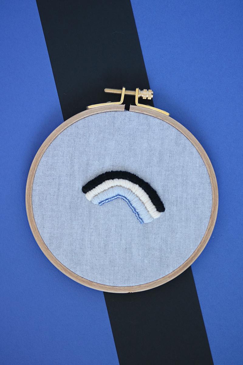 Cadre décoratif Arlo, broderie réalisée à la main, en France, sur du tissu upcyclé. Ces teintes sont le gris, le bleu, le beige et le noir.